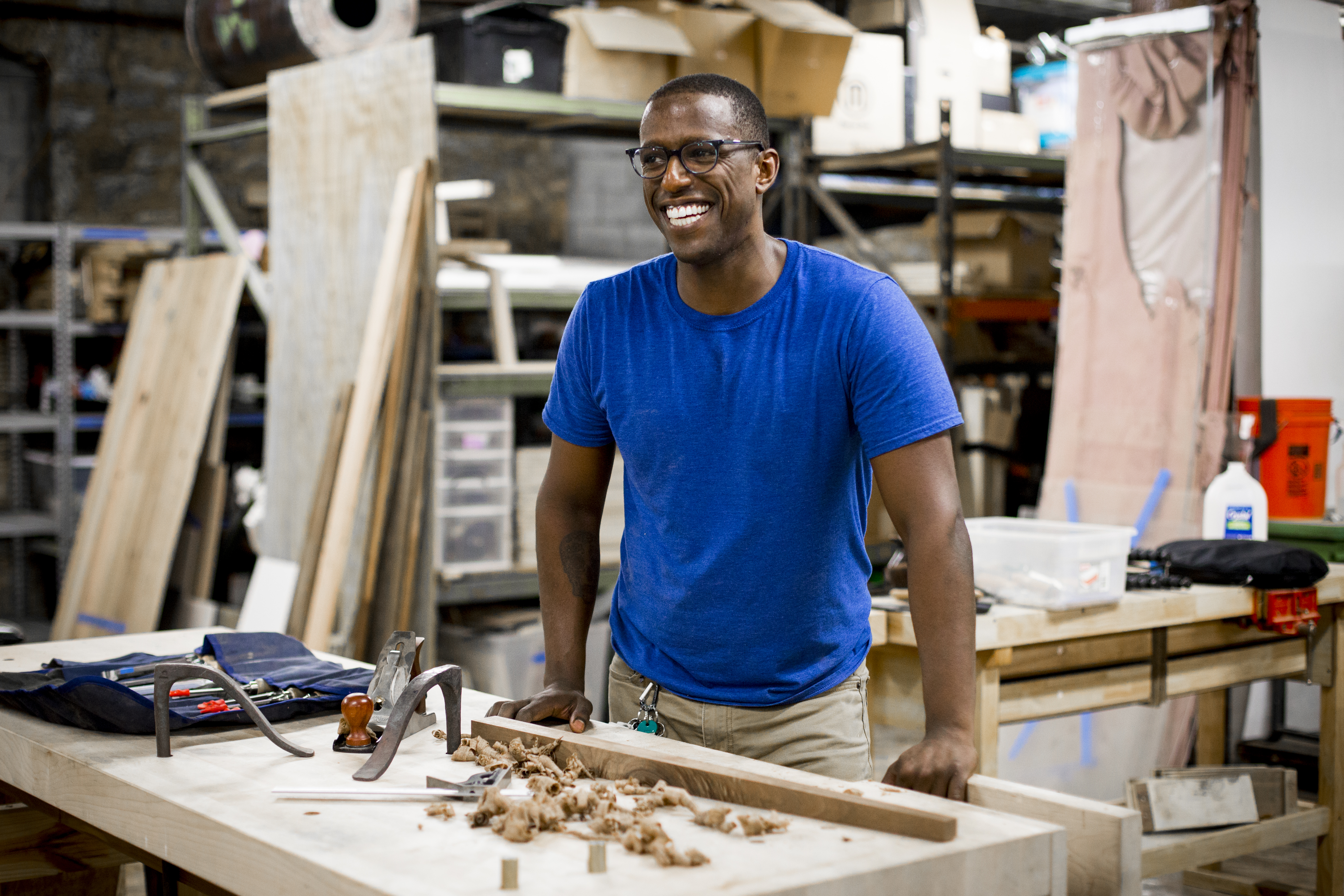 Robell smiling and standing at a workbench. On the bench is a table leg and wood shavings.