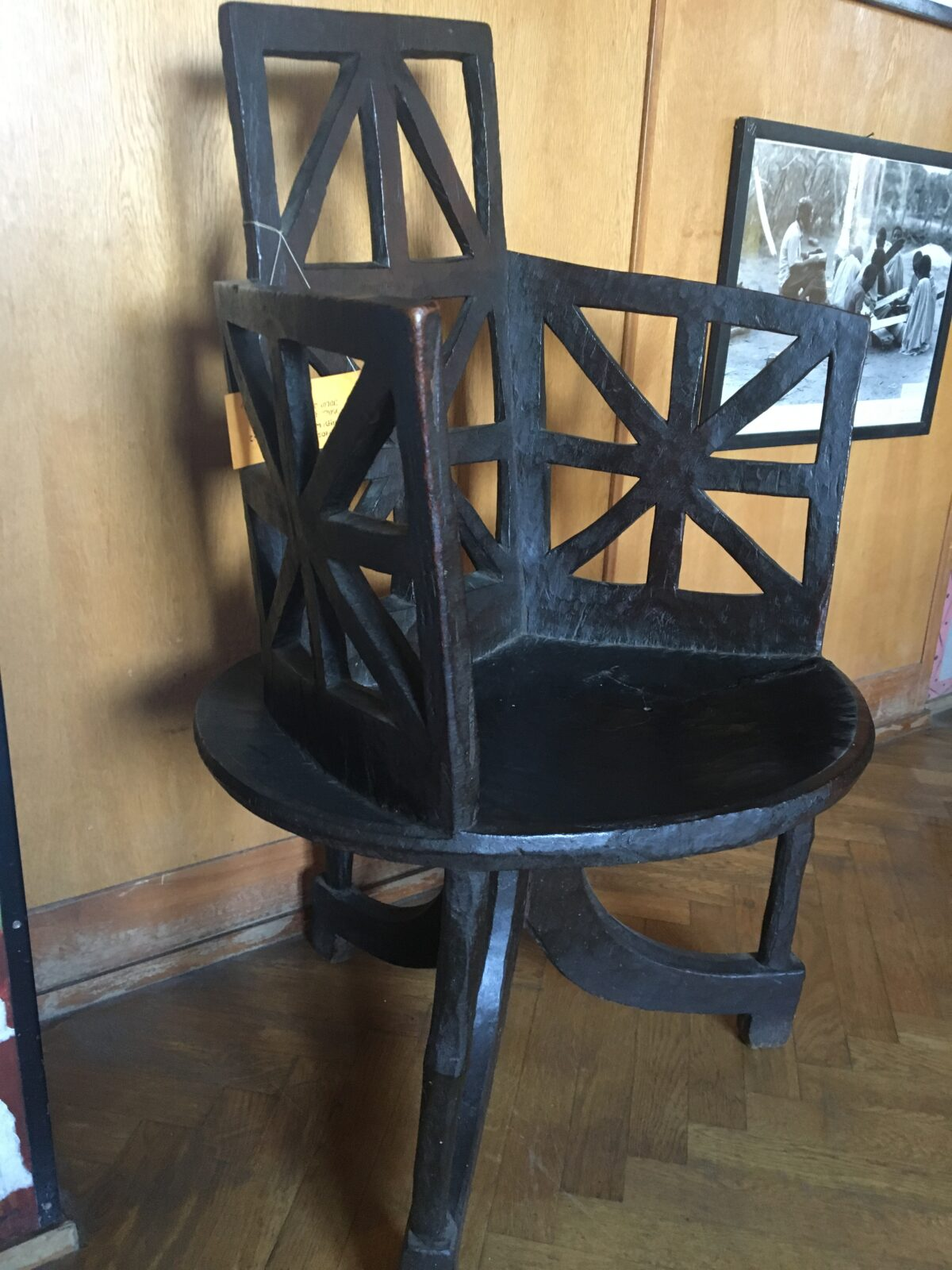 A very dark wooden chair with three swopping legs, a saucer-shaped seat, and a pierced-carving starburst pattern on its back rest and under its arms.