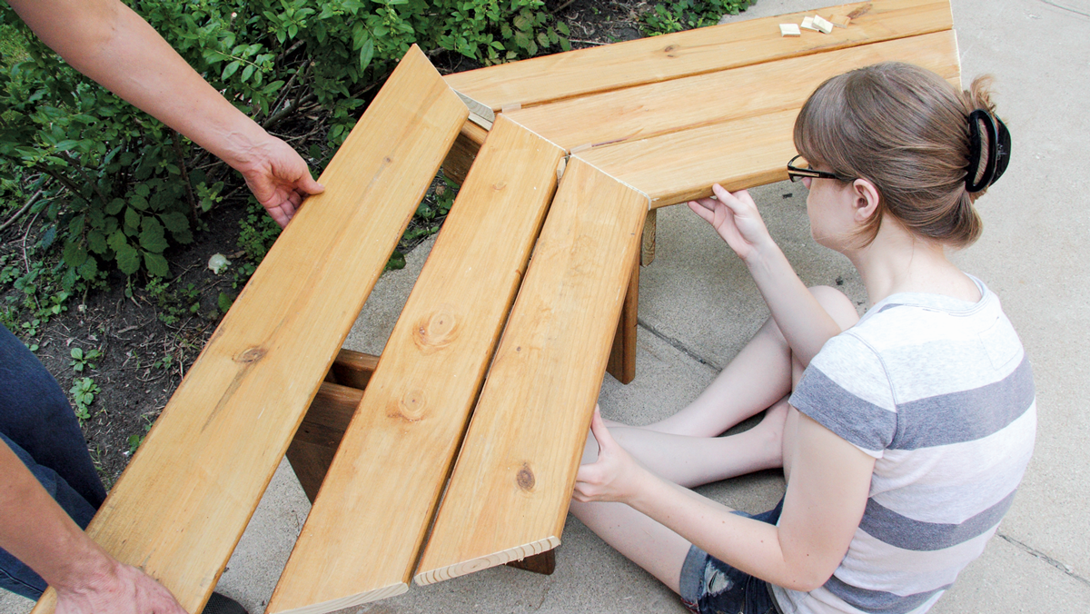 Working on a flat surface, start assembling; this is much easier with a helper or two.