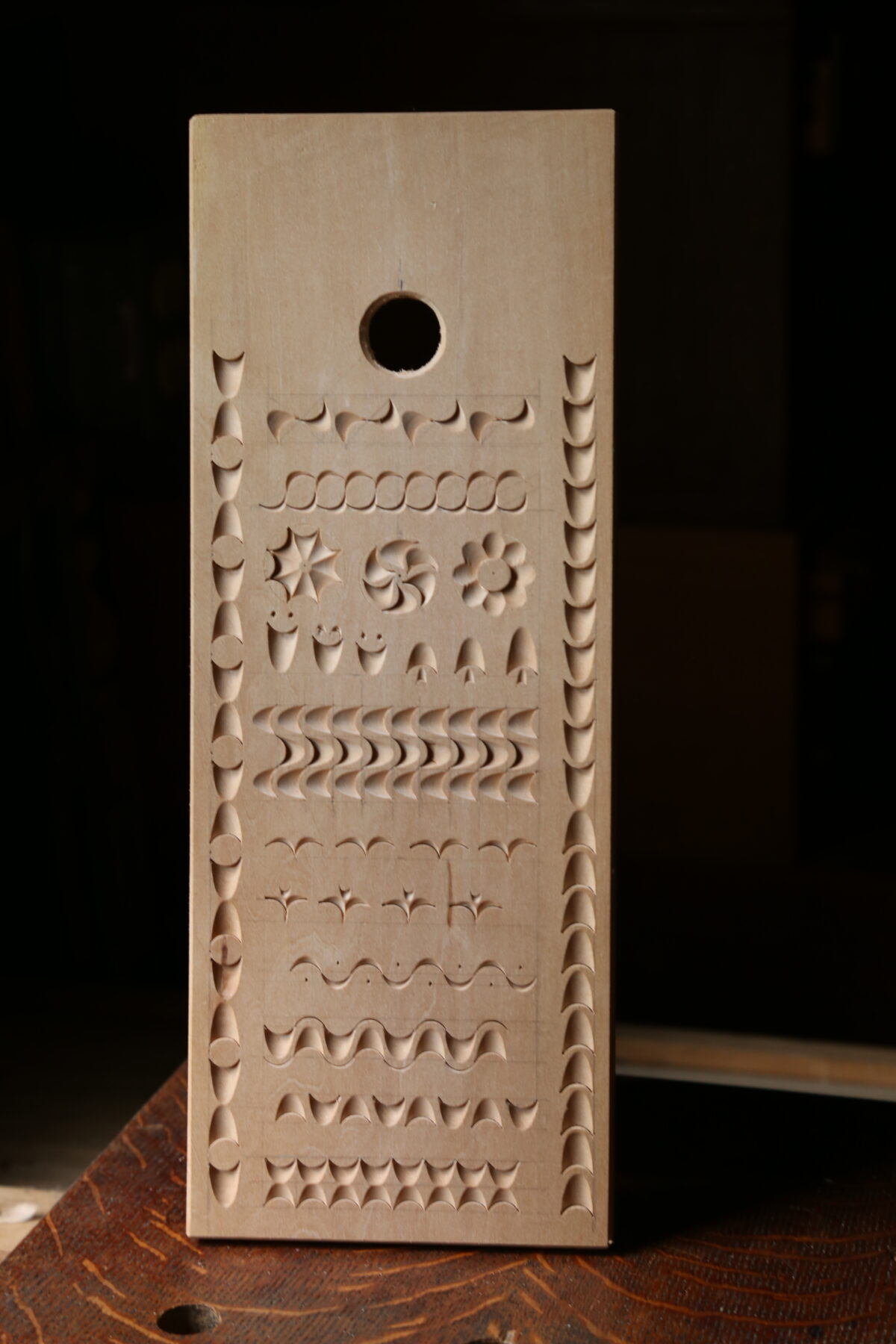 A narrow basswood board featuring different patterns carved with a single gouge. Light rakes across it from the left, showing deep shadow contrasting against the light basswood.