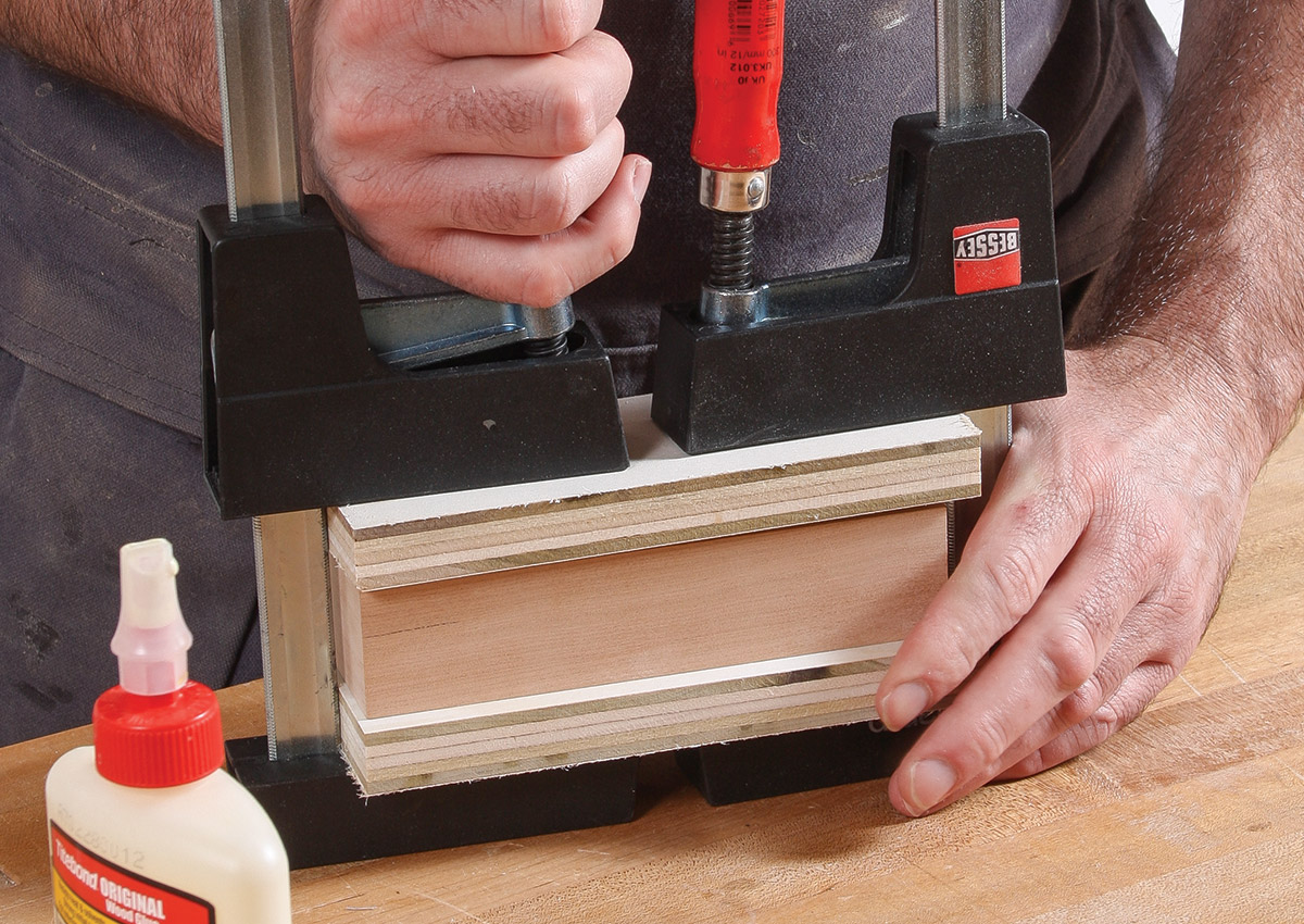 Using cauls to protect the edges, clamp the bottom to the box