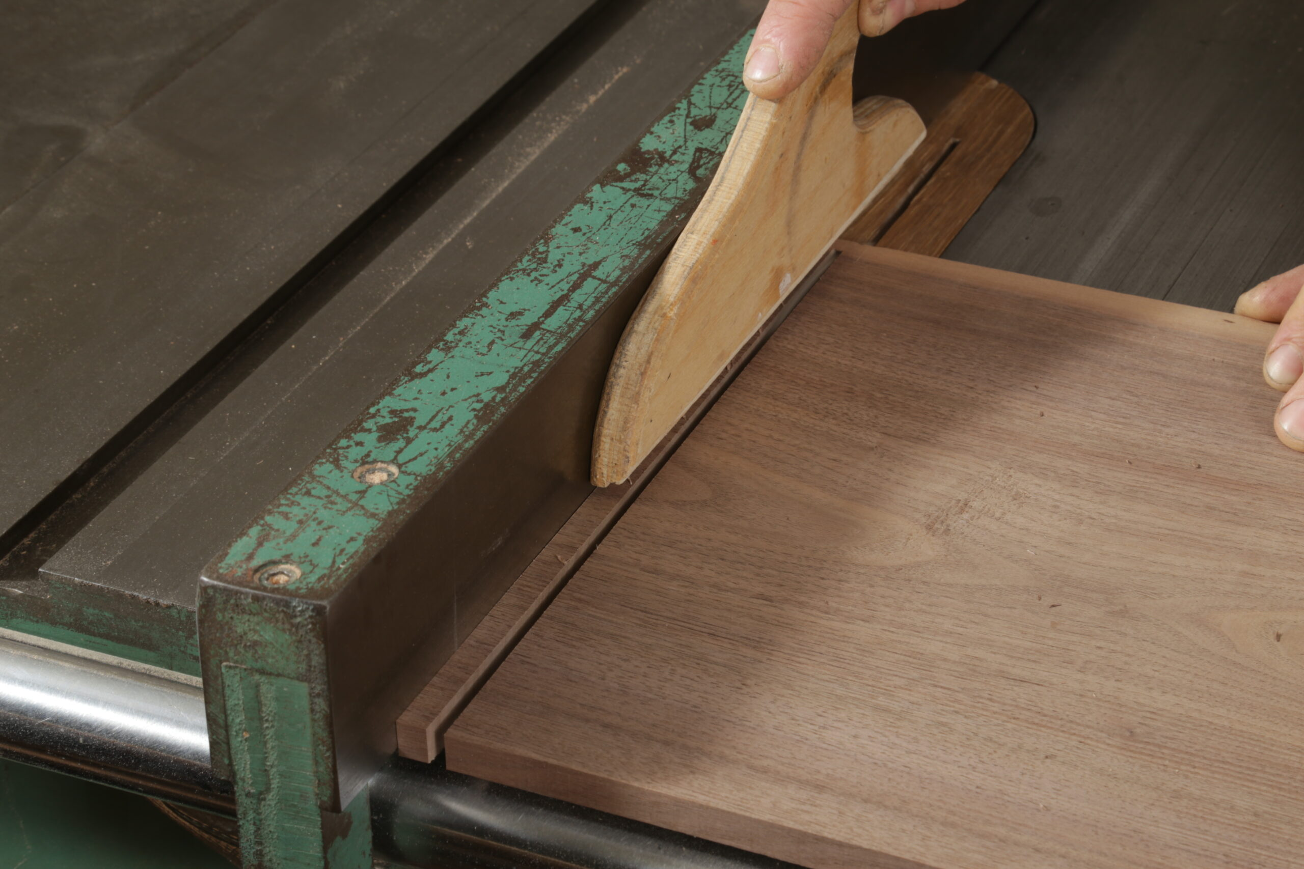 The author crosscutting a narrow strip from the end of a walnut board. This strip will be a runner for drawers. or safety, he is using a push stick to keep his right hand away from the blade.