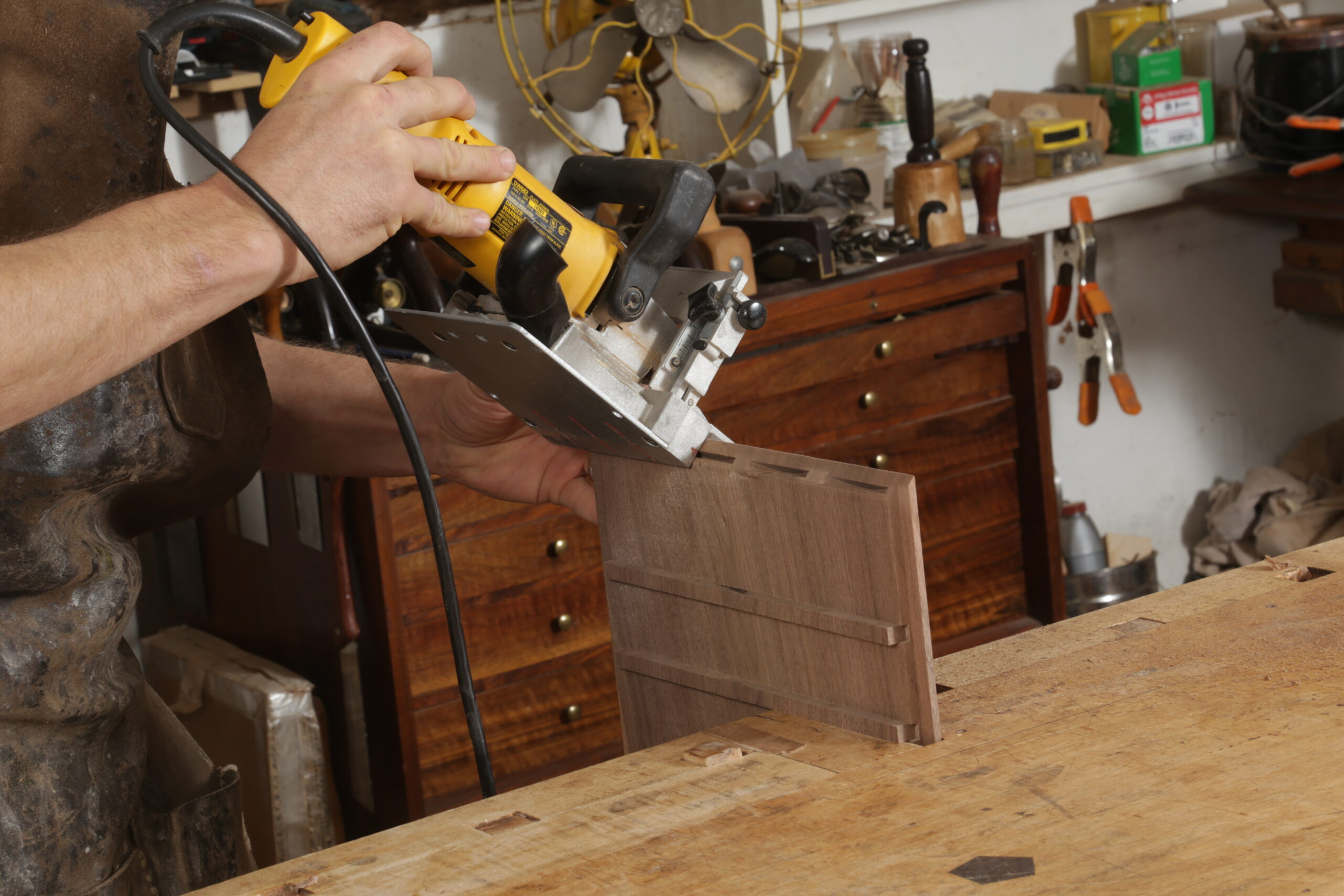 With the box held upright at the workbench, the author is using a biscuit joiner to cut slots in a mitered end. The slots are thin, and there are four of them along the miter. The biscuit joiner is predominantly yellow.