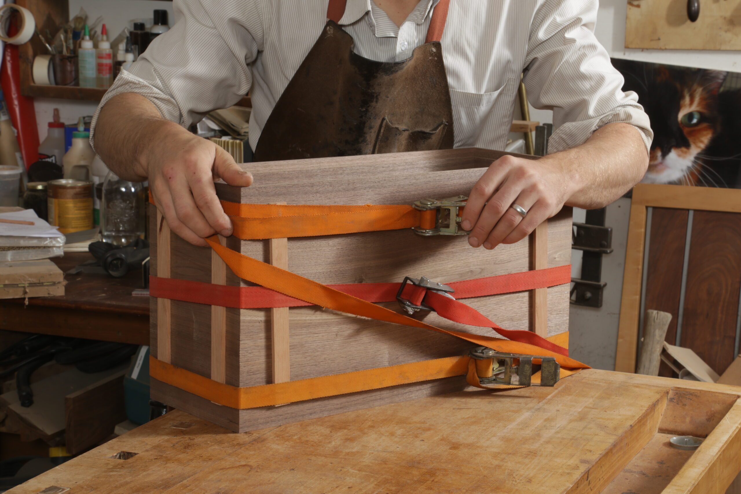 The box carcass is assembled, and the author is clamping it up. He is using two orange ratchet clamps and one red one to apply clamping pressure. At each of the box's corners are two strips of wood between the box and the straps.