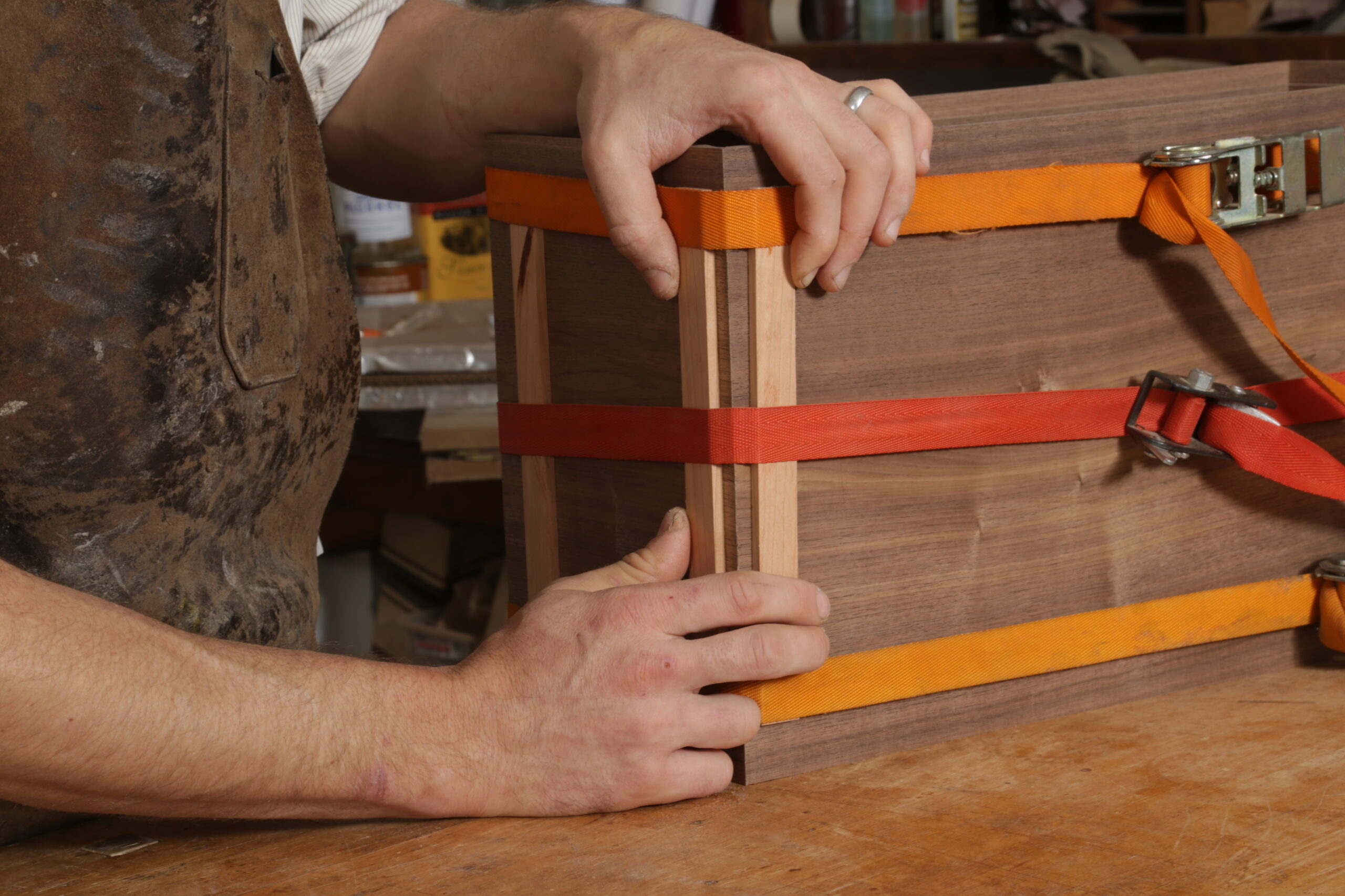 After tightening the ratchet straps, the author is pinching two strips of wood toward a corner of the box.