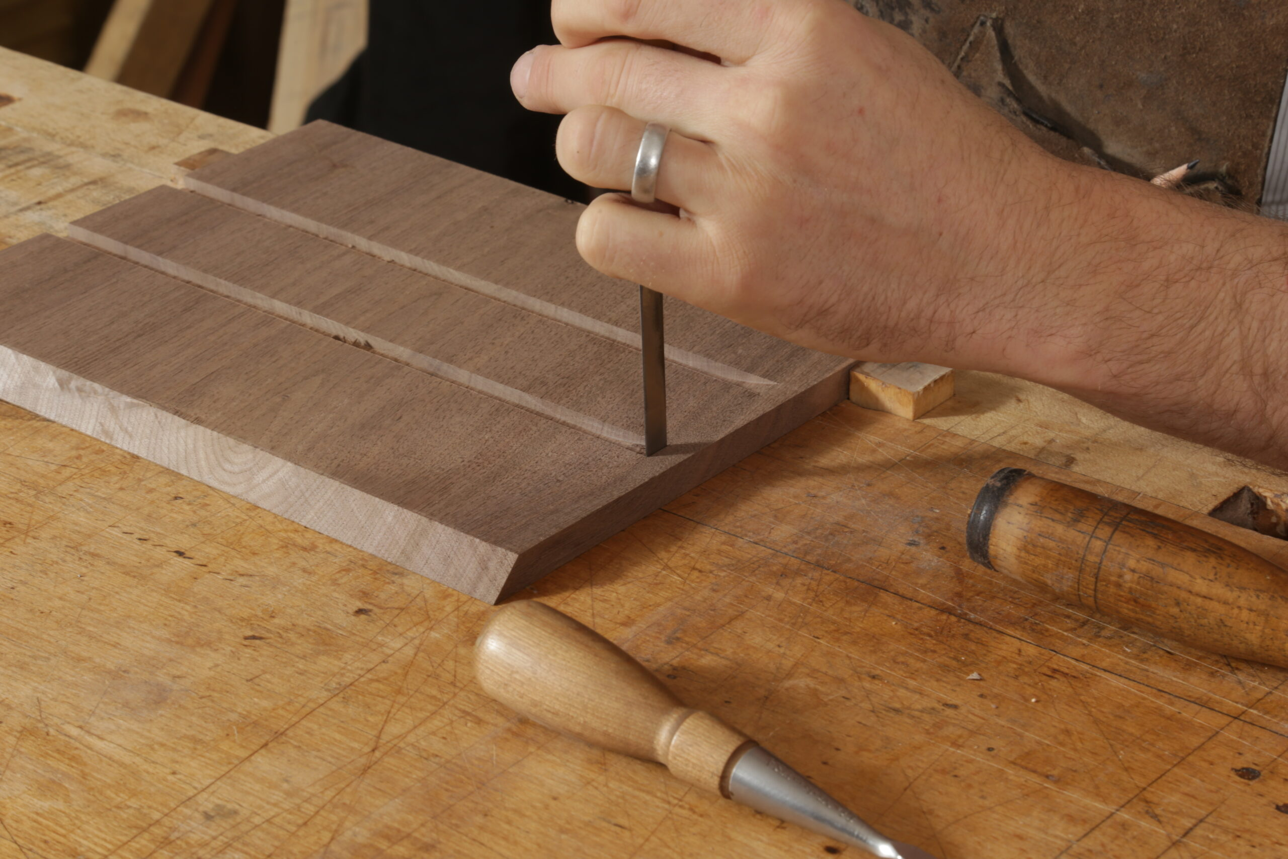 The author using a chisel to square up a dado. He is holding one chisel in his hand, and the handles of two others are in shot. There are two dadoes on the inside of the box side.