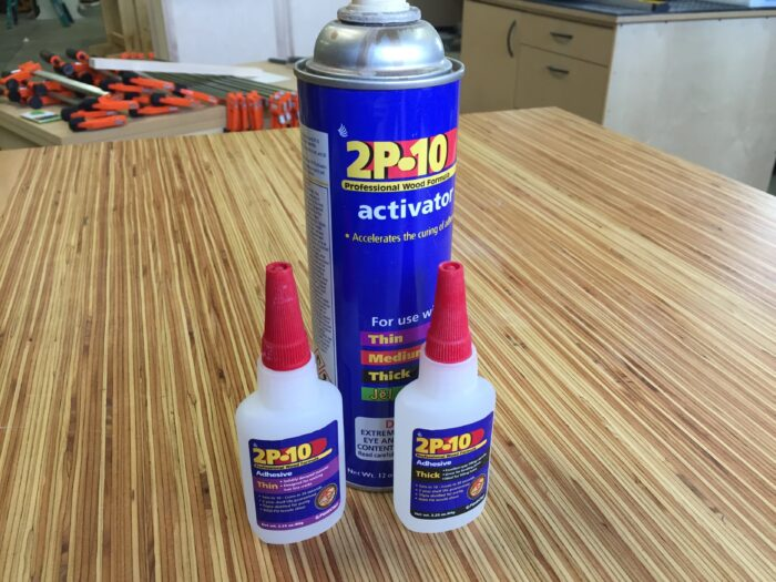 Two bottles of ca glue and a spray can of activator.