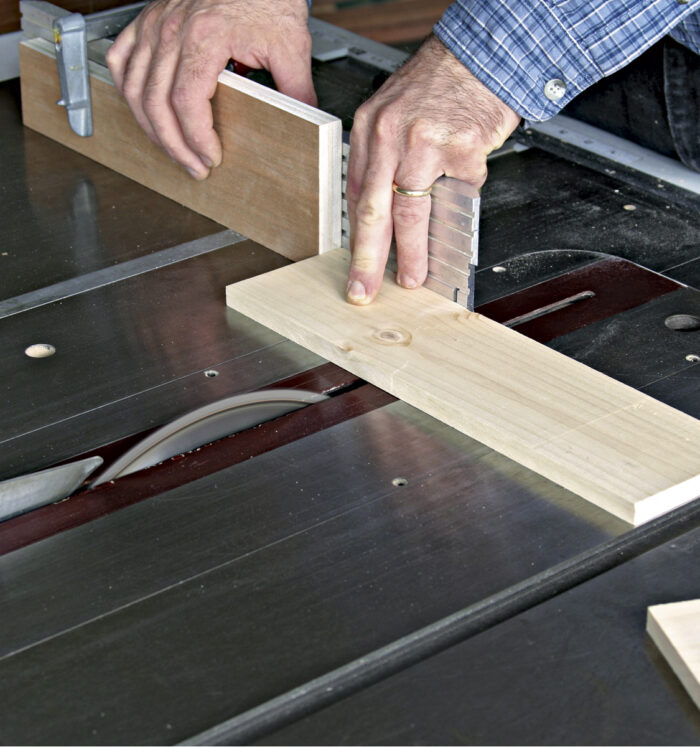 Stop block is clamped to the miter gauge to get the boards the same length.