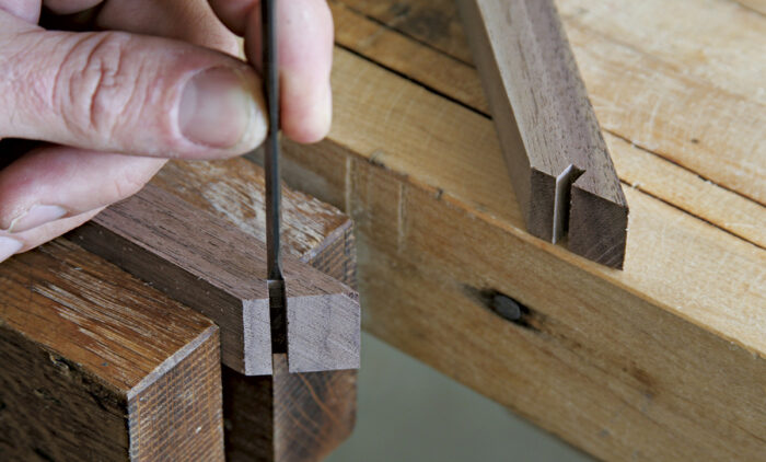 A small chisel is used to flatten the bottom of the spline kerf.