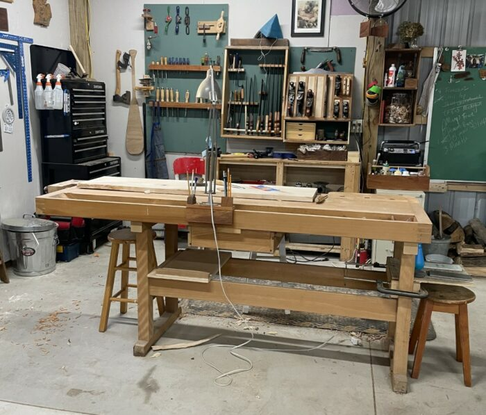 A long workbench in a light-color wood. In the background are green walls and assorted woodworking tools.