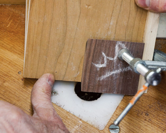 To begin the cut, lower the jig and workpiece over the router bit with the jig held firmly against the fence and stop block