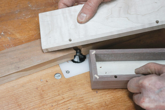 Using a chamfering bit in the router table to make the relief cut in the back edges of the lid and body of the box