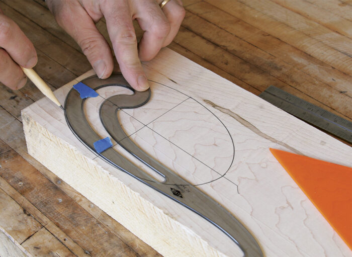 Use a French curve to draw the oval on the board.