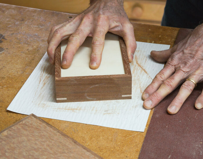 Using sandpaper on a workbench to sand box edges