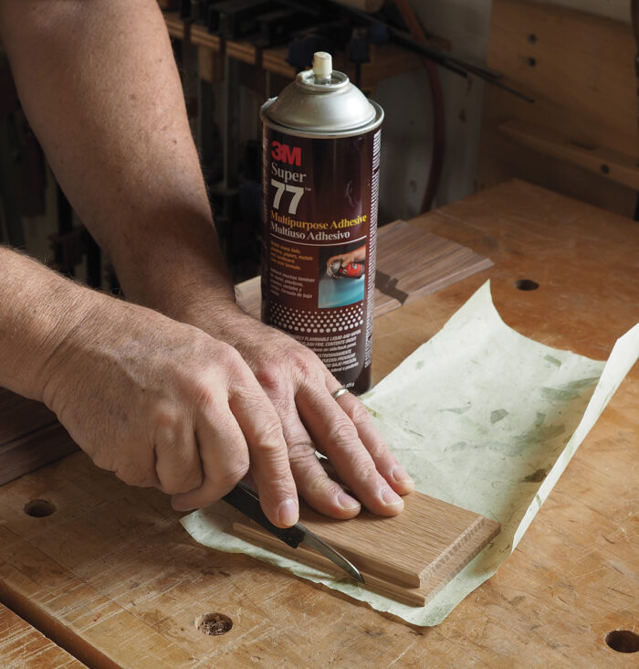 It's easiest to spray the box bottom with a light mist of adhesive, drop it onto the paper, and trim around it.