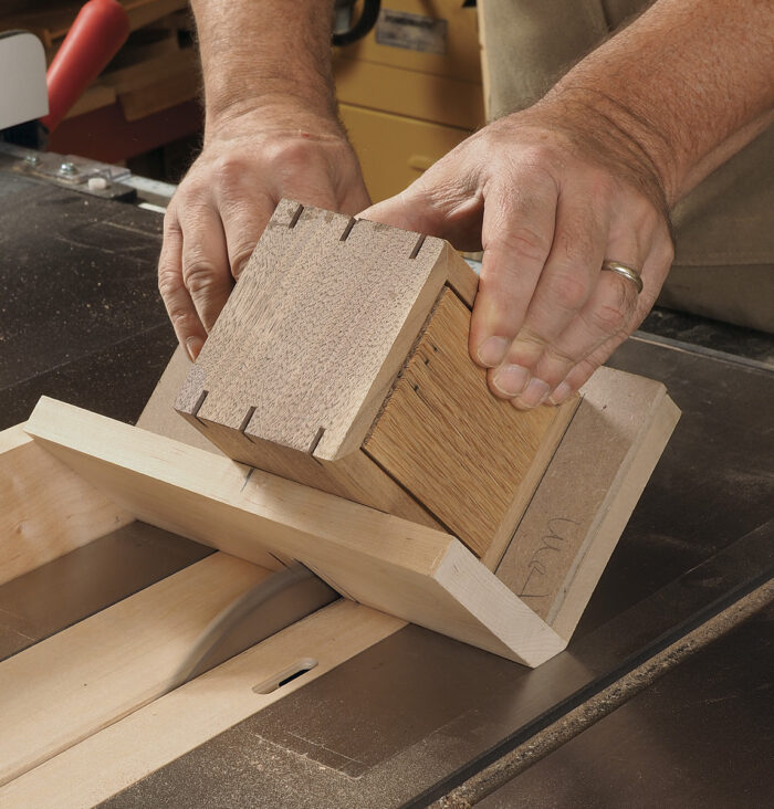 Use a jig that supports the box at 45° to cut slots for splines.