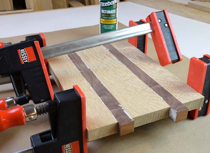 five boards glued up held together with clamps.
