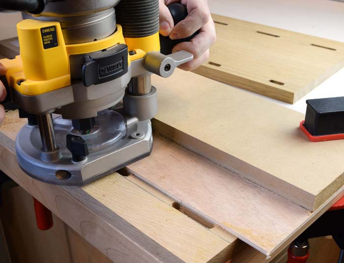 A yellow router sitting on a board routing mortises into the board.