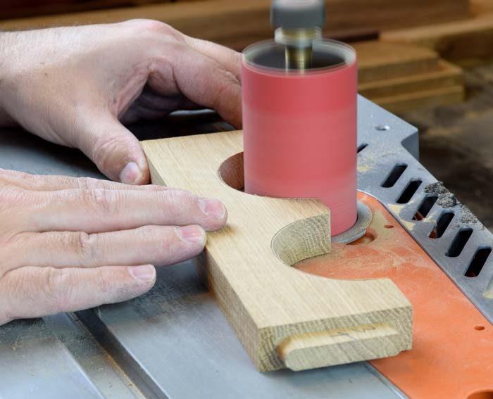 sanding a curve into a wooden piece with a spindle sander