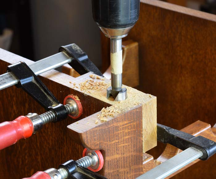Using a forstner bit to drill into the end grain of the rack for a figure eight fastener