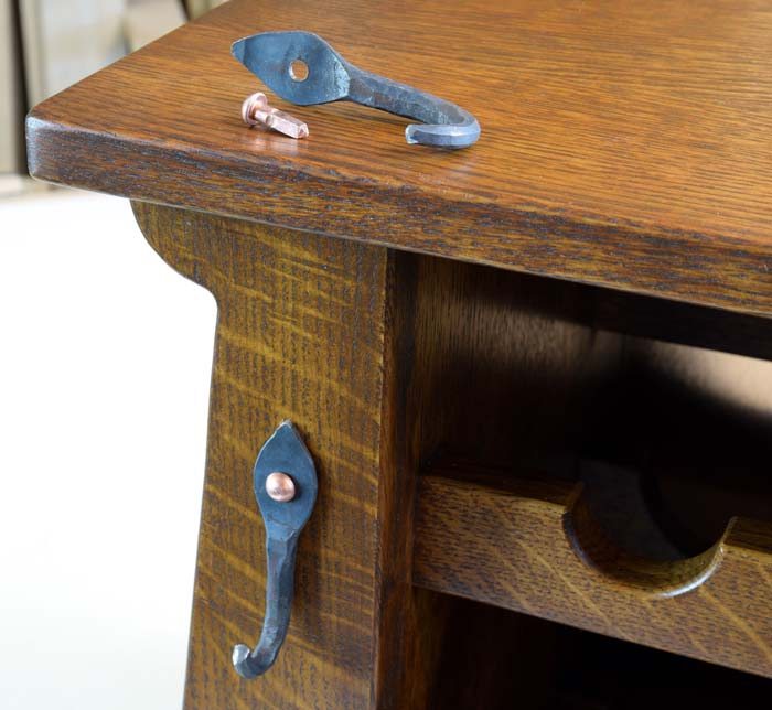 Metal hanger sitting on top of cabinet and one mounted to the front with a copper nail