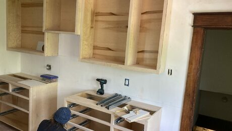 a craftsperson bent down installing something in a kitchen that is being renovated