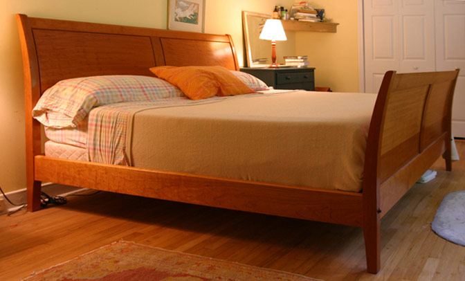 A wooden bed softly it by a lamp