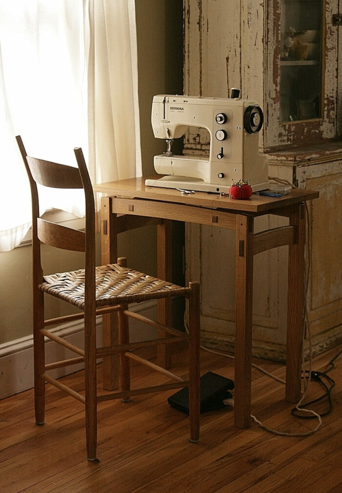 Sewing table with sewing machine on top of it. Next to a wooden chair.