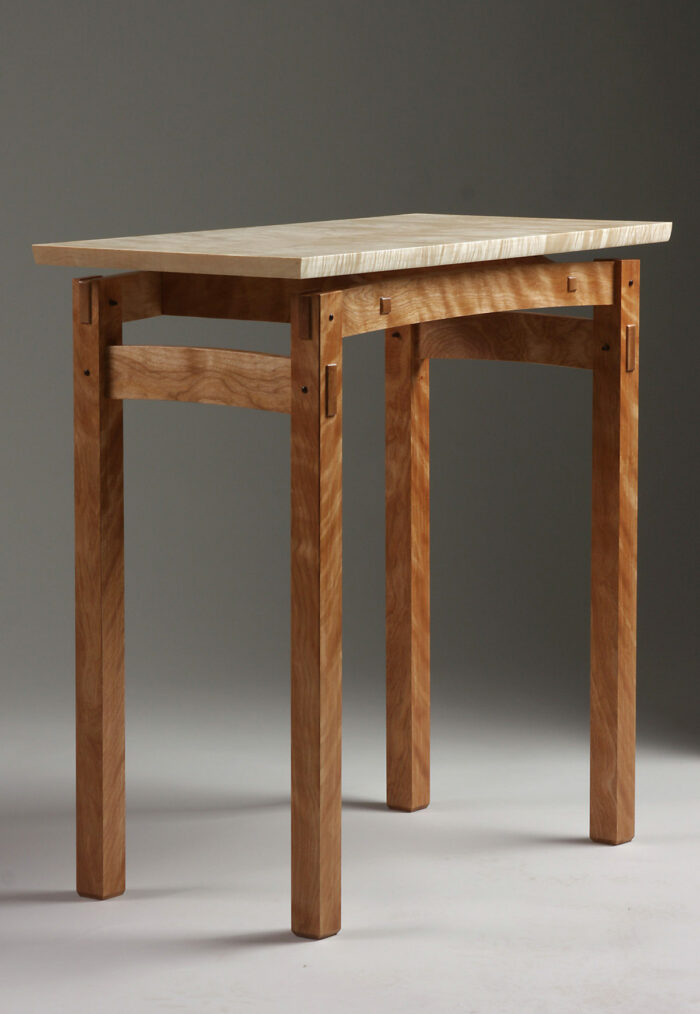 Wooden table with a redish base and a lighter colored top