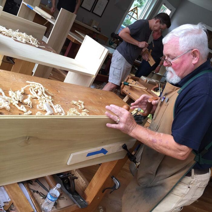 A man using a grooving plane to create a tongue and groove joint on a piece of poplar