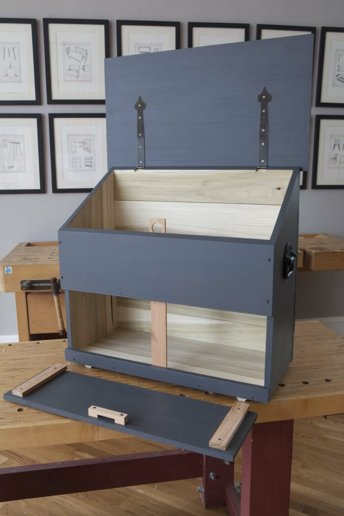 An empty tool chest sitting on a bench with the lids open.