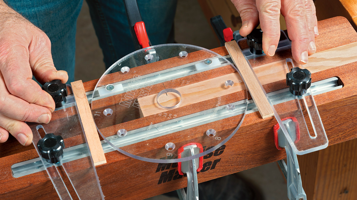 Setup is simple. The router rides on a round polycarbonate slide plate, and two adjustable fences limit its travel. With the slide plate centered, you set the stops by inserting two small shopmade spacers.
