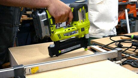 Cordless brad nail gun driving a nail into the bottom of a drawer