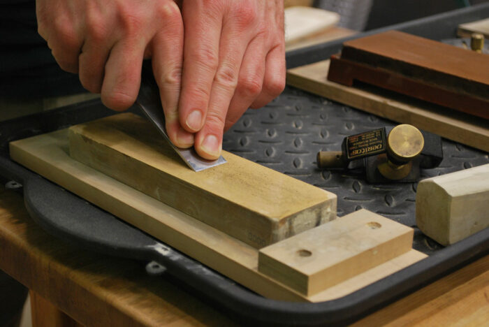 A chisel being sharpened on a water stone with a honing guide off to the side.