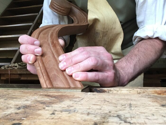A curved piece of wooden molding is being held against a flat piece of metal.