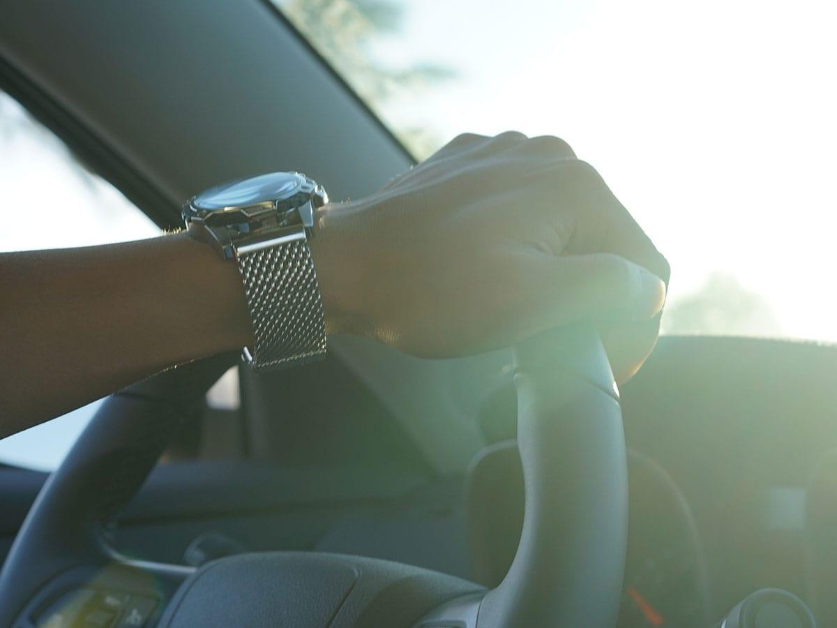 Man's hand on a steering wheel, wearing a silver watch