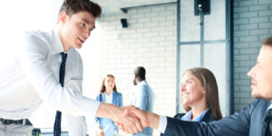 Employer shaking hands with potential employee trying to avoid communication failures