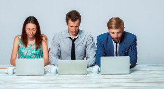 Millennial professionals searching for career management tips on their laptops.