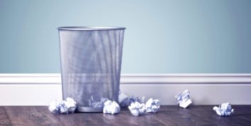 Trash can surrounded by crumbled paper filled with job seeker New Year's resolutions to ditch.