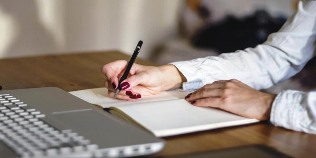 Woman writing with a pen and paper writing down tips for first-time telecommuters