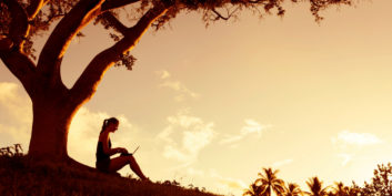 Woman under a tree reading success stories of inspiring job seekers.
