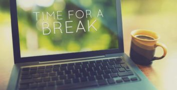 The laptop and coffee cup of a employee experience job satisfaction and lower stress due to flexible work.
