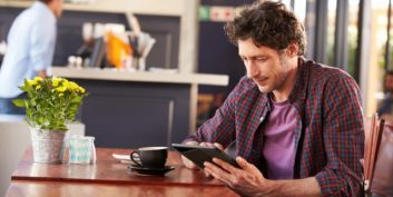 Man at a coffee shop reading articles about flexible and remote jobs