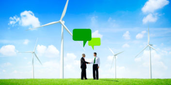 Two businessmen in a wind farm talking about the state of green jobs.