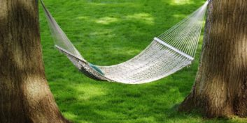 Employees getting in a hammock achieving work-life balance.