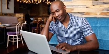 Man in coffee shop learning how to get started freelancing.