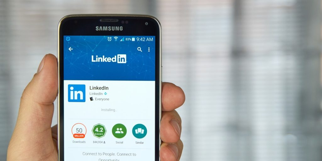 Job seeker on a mobile phone avoiding disastrous LinkedIn mistakes.