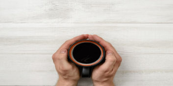 Hands holding coffee cup to improve mood and job performance.