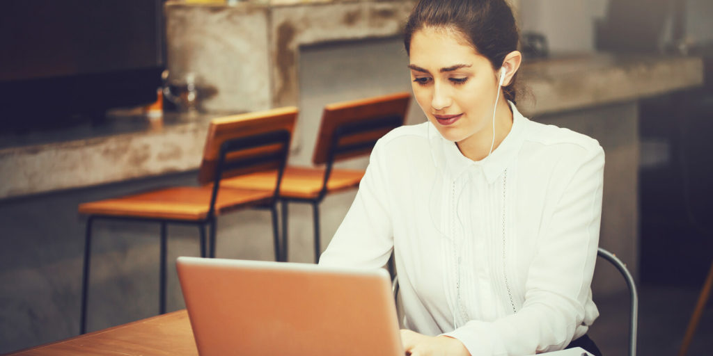 Woman trying to avoid distraction and stay focused at work.