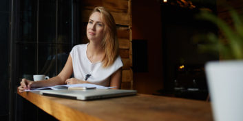Woman in a coffee shop trying to find a strong career fit.
